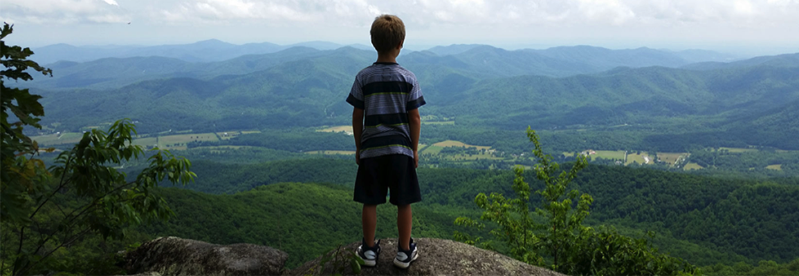 child standing at mountain overlook